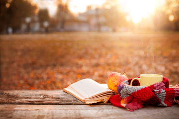Open book, apple and tea cup with warm scarf