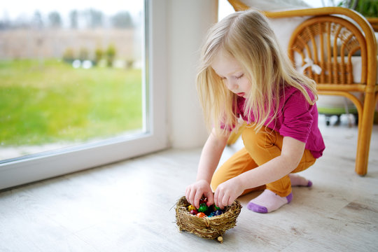 Cute little girl playing with colored Easter eggs at home on Easter day