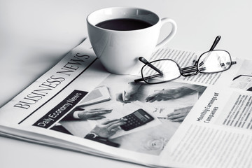 Newspaper with eyeglasses on white table