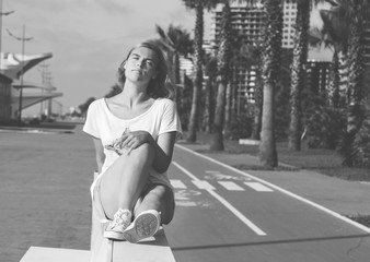 Portrait of teenage girl while sitting on white bench. Blonde, young girl near bicycle path with tall palms. Sunny summer days. Black and white portrait