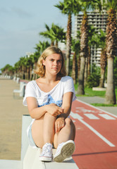 Portrait of teenage girl while sitting on white bench. Blonde, young girl near bicycle path with tall palms. Sunny summer days