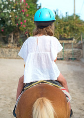 Portrait of little girl riding pony. From the back.