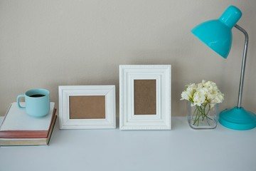Picture frames, coffee cup with table lamp and flower vase