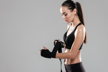 Side view of Serious Young Sporting woman in boxing bandages