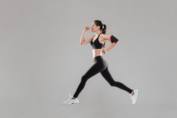 Pretty young fitness lady running over grey background