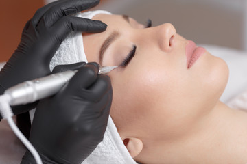Close up cosmetologist making eyeliner permanent makeup