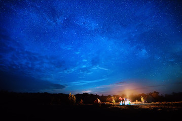 Camping fire under the amazing blue starry sky with a lot of shining stars and clouds. Travel recreational outdoor activity concept.