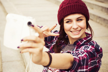 Sporty casual stylish hipster woman on a skateboard in comfort outfit, in a hat and glasses outdoors make selfie