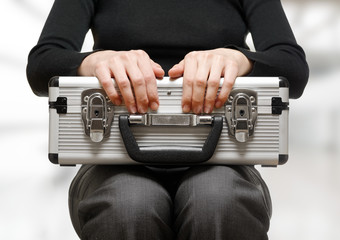 Business woman holding an aluminium briefcase