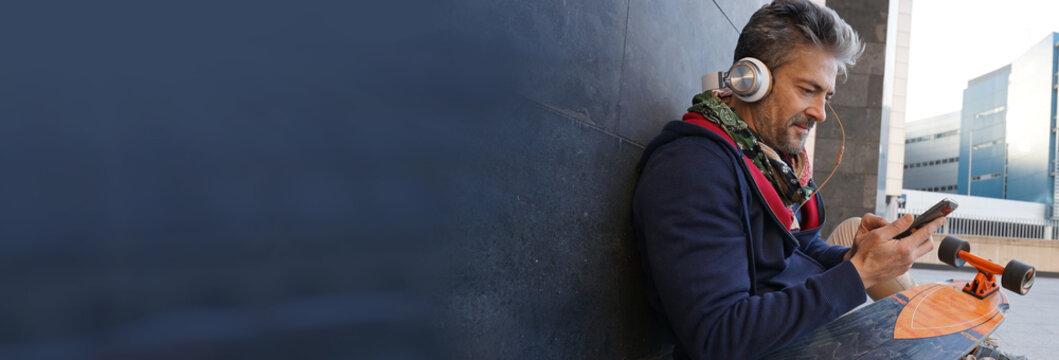 Skateboarder sitting in urban area listening to music