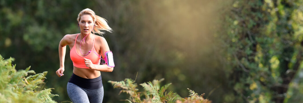 Beautiful athletic woman running in forest