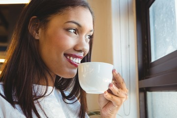 Smiling woman having cup of coffee in office