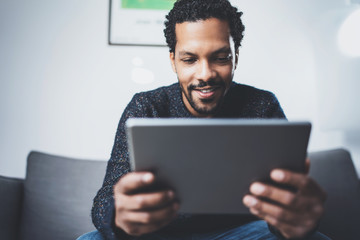 Selective focus.Attractive bearded African man using tablet while sitting on sofa in his modern office.Concept of young business people working at home .Blurred background.