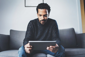 Attractive bearded African man using tablet while sitting on sofa in his modern office.Concept of young business people working at home.Blurred background.