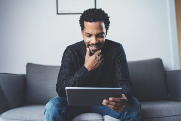 Cheerful African man using pc tablet and smiling while sitting on the sofa in his modern room.Concept of young business people working at home.Blurred background.