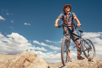 Biker traveler with bicycle in Himalayas mountains