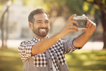 Happy young man taking a self portrait outdoors