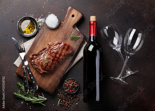 Wall mural Grilled ribeye beef steak with red wine, herbs and spices
