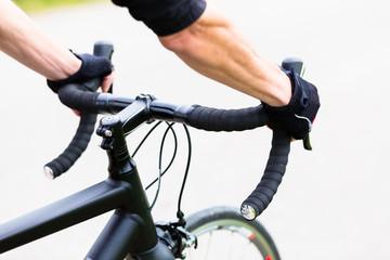 Sportler hat Hände am Lenker eines Rennrades, Rennlenker, Detail