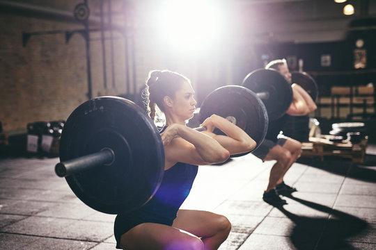 Man and woman lifting barbells at gym