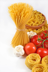 Uncooked Italian pasta, ripe tomatoes branch and garlic on a whi