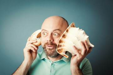 Bearded middle-aged  man with shell listening noise of sea