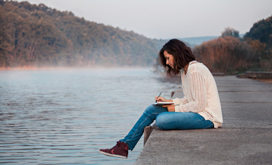Girl writing diary by the lake in the early cold morning.