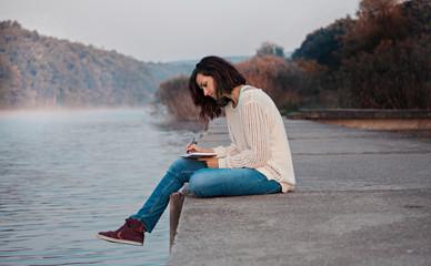 Creative writing. Student sitting by lake, writing poem.