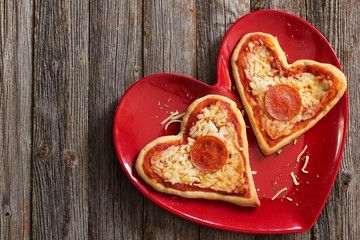 Two mini heart pizzas served in heart shaped red plate, top view