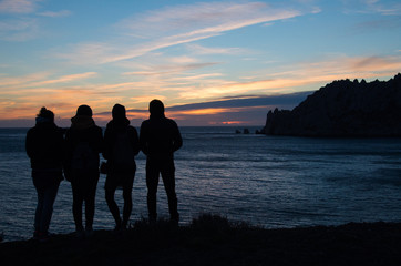 four friends watching the sunset on the sea