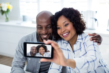 Happy couple taking selfie on mobile phone in living room