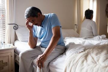 Tensed senior man sitting on bed