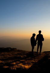 Silhouette of lovers waiting for sunrise sunset on mountain whil