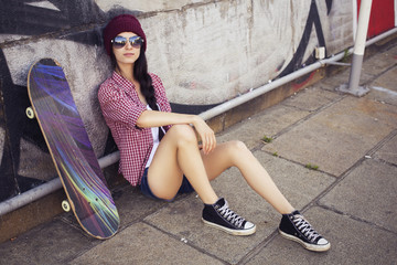 Brunette teenage girl in hipster outfit (jeans shorts, keds, plaid shirt, hat) with a skateboard at the park outdoors. Copy space