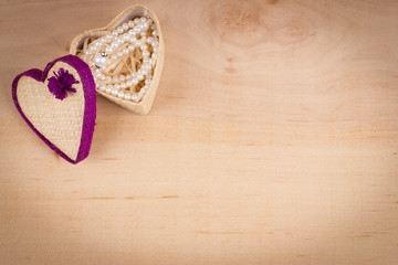 Elegant valentine background with white pearls and gift box shaped of heart on wooden background. Empty space for text