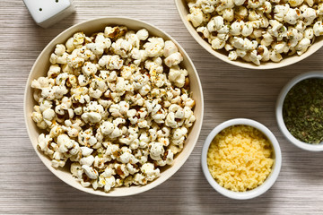 Homemade fresh savory popcorn with cheese, garlic and dried oregano in bowls, photographed overhead with natural light (Selective Focus, Focus on the top of the popcorn)