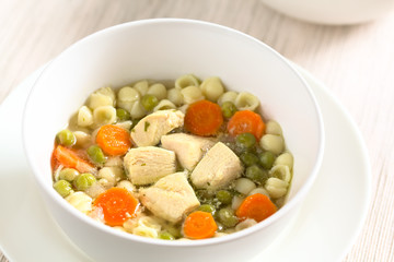 Homemade chicken soup with pea, carrot and small shell pasta in bowl, photographed with natural light (Selective Focus, Focus in the middle of the soup)