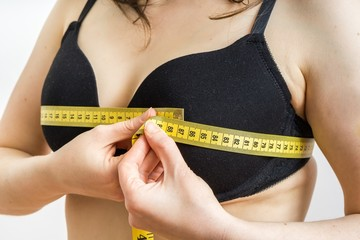 Woman is measuring her breast size with a tape.