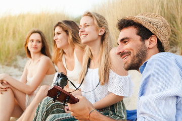 Beach at sunset in summer. Group of young friends are to relax, man plays guitar while the beautiful women smile