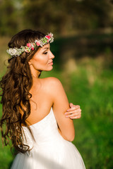 Beautiful bride in wedding dress and with a lovely mood in nature