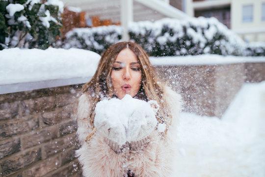 Winter portrait of beautiful woman blowing a snow outside on winter, snowy day.