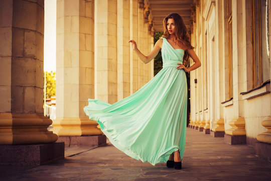 Beautiful blonde with a long curly hair in a long evening dress in motion outdoors near retro vintage building in summer sunset. Copy Space