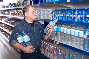 Portrait of glad man buying a water