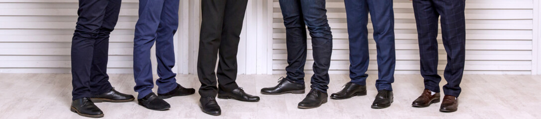 Six men's feet in black leather shoes