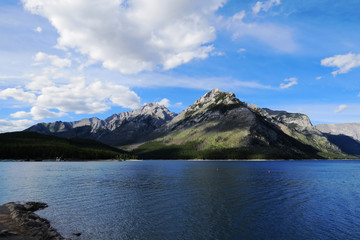 A distant landscape with a crystal clear lake surrounded by nature and a mountain. Banff, Alberta, Canada.