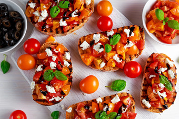 Tasty Traditional Tomato bruschetta with feta cheese topping, fresh basil and balsamic vinegar