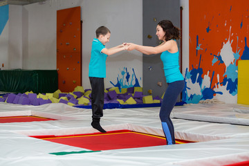 Mother And her son jumping and Bouncing On Trampoline Together