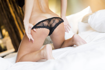 Buttocks of slim young woman in black lingerie