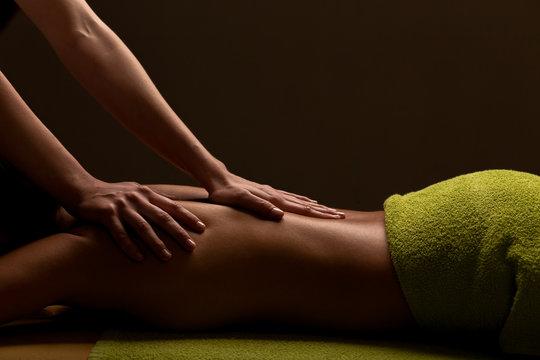 close-up masseur hands doing back massage in spa center. low key