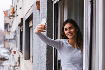 Girl taking selfie at an open window